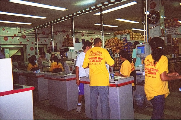 This photograph shows a row of female cashiers in a supermarket in Sao Paulo, Brazil sitting in chairs while they work at their tills.